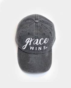 """Unstructured hat with our """"Grace WIns"""" design. One Size fits Most. Velcro closure *Coal hat with white embroidery. Christian Hats, Christian Clothing, Christian Women, Christian Apparel, Grace Wins, Sisters In Christ, Stitch Fix Outfits, Wearing A Hat, White Embroidery"""