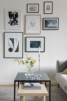 A wall gallery with light wood & black frames