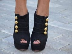 Black heels with gold buttons.