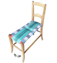 Elongated the seat to make a child's chaise longue from an old French country chair. Blues going one way and greens going the other, interspersed with red. A pair of sunglasses to add perspective.