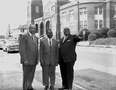 """Dr. J. L. Patton, Jr. [principal of Booker T. Washington High School), African Price, and Rev. I. B. Loud [pastor of St. Paul Methodist] stand on the street in front of St. Paul Methodist Church."""
