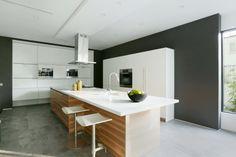 un îlot élégant en bois avec un coin repas dans la cuisine en blanc et gris