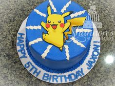 Buttercream Pokemon cake with fondant Pikachu and detailing. Chocolate cake with raspberry buttercream filling and blue, vanilla buttercream frosting.