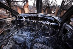 Burnt houses can be seen from inside a burnt-out car.