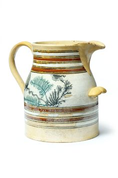 """YELLOWWARE PITCHER. American, mid 19th century. Bands and two-tone seaweed design. Shell-shaped handhold. Imperfections. 10.5""""h. Ex Clark Garrett, lot 579, at Mike Clum Auctions, June 2002. Estimate $1,000-2,000 garths.com"""