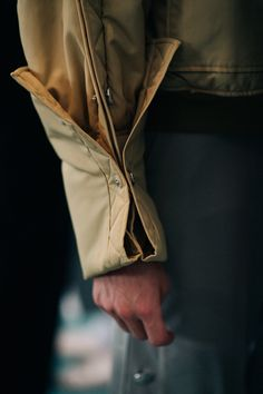 A sleeve of a beige jacket