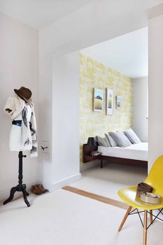 The guest bedroom features an original mid century Danish Rosewood bed; vintage dress makers dummy and original Eames shell chair in canary yellow, continuing the yellow accent created with the Cole & Son Cow Parsley wall paper.