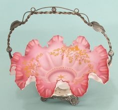 *BRIDE's BASKET: the fancy silver frame seems to be signed S.C.P. Co. Conn. The lovely glass insert has a ruffled edge + exhibits various gradations of pink. It is hand decorated with a gold + white enamel design. The outside is white, c. 1870.