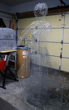 So I decided to give this a try:  Chickenwire, various fabrics, a LED flicker flame tiki torch, various wire.  I followed a tutorial by Shawn and Lynne Mitchel.  Here is the framework:and here she is in the garage undergoing a dry run before getting a coating of scotch guard and moving to the cemetery: