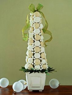 """CAN ADD SO MANY OTHER CANDIES/SWEETS TO DO THIS: Purchased icing is the """"glue"""" that keeps these decorations edible. Place floral foam in a container, then insert a wooden skewer in the center. Push a foam cone onto the skewer, then cover with purchased icing. Attach purchased meringues using wooden picks. Finally, tuck bay leaves between the meringues and container."""