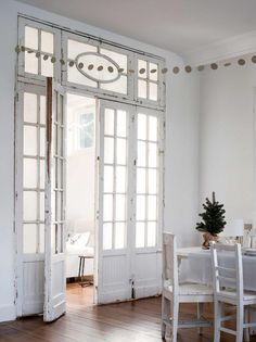 Une grande porte vitrée comme une verrière, entourée de bois