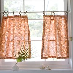 Consider this clever alternative to cafe length curtains: Use curtain rings with clips to hang pretty dishtowels or napkins on a curtain rod.