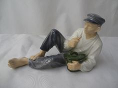 Royal Copenhagen Figure Of A Boy with a CapReclining While Eating. Made in Denmark with Royal Copenhagen Seal and Paper Label.