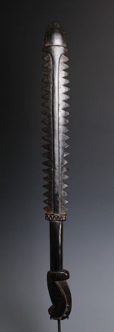 Serrated edged, sword shaped war club. From New Guinea.