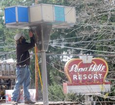 Nate Berry of Sterling Builders unbolts the Westinghouse lamps from atop its pole at the former Penn Hills property in Analomink on Tuesday, April 21, 2015.
