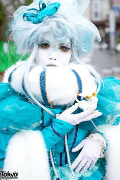 Japanese shironuri artist Minori on the street in Harajuku with a vintage and handmade look features faux fur collar & attached tassel scarf, blue top, lace up platform boots & a small cat.