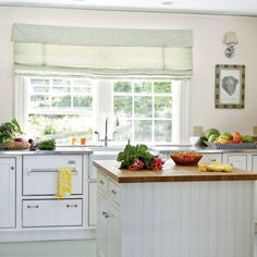 Installing one mega shade effectively creates the illusion of a single, large-scale window. Here, a subtle valance, sweetly dotted fabric, and a Roman-style shade hanging above these kitchen windows smooth out the room's prevailing straight edges.