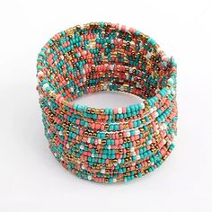 Beaded Bohemian Cuff Bracelet Multi-strand, multi-color boho cuff bracelet. Sold in original packaging. Colors of bracelet include, aqua, coral white & gold tone. Size: Adjustable. Please ask if you have any questions about this item. Jewelry Bracelets