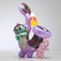 The Heady Sherlock Pipe by Sweet Shop and Steller Glass. This one-of-a kind pipe features Pink Slyme glass, 4 worked sections and sweet heady glass attachments. This hand pipe has a one hole push bowl with the carb on left side.