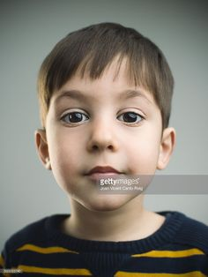 Studio portrait of a caucasian young boy from Spain looking at camera...