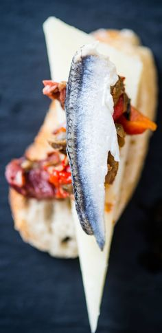 Pope Pairing: El Boqueron Bonito!  1605 Manchego, topped with a blend of chopped Kalamata olives, roasted red peppers, and tomato vinegar, garnished with a white anchovy, on ficelle.