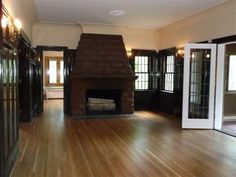 not sure which i love more...  the floors, the multi-paned windows, the wood door frames or the fireplace out in the middle.