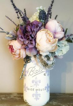 Shabby chic home decor | handpainted mason jar with fleur de lis accent | pink and purple silk floral arrangement | modern farmhouse rustic style decoration | chippy distressed paint | #affiliate #shabbychic #farmhouse #rustichomedecor