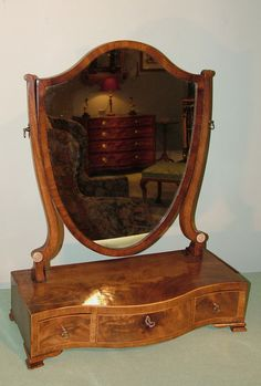 A late 18th Century well-figured mahogany shield-shaped Toilet Mirror supported on serpentine boxwood strung base fitted with 3 drawers, raised on ogee bracket feet. Circa: 1780 Ref: 5592