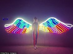 Glowing: Katy Perry posed in front of a display piece of neon glowing wings…