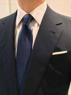 Navy suit, white shirt with light grey stripes, navy tie with white pin dots
