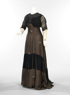 Circa 1910 Jacques Doucet dress, Paris. This dress is not typical of the work produced by the House of Doucet, for its choice of fabric is extremely modern. The randomly spaced white polka dots printed on the bronze chiffon add an artistic touch. The fringe is an unusual decorative element as well, that exhibits an adventuresome element.