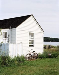 Love this cottage with white cladding on the lake / beach shore and old vintage bike
