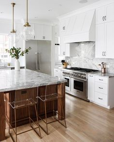 White marble kitchen with gold and wood