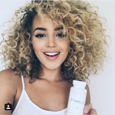 I'm really into blond dyed curls with roots. This layered cut with bangs is hot..