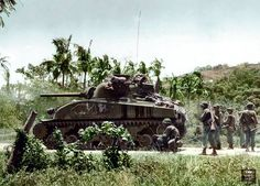 An M4 (Composite) Sherman tank and combat soldiers of the U.S. 37th Infantry Division cautiously probe the area for Japanese defenders in Luzon, the Philippines. January, 1945.
