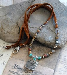 A long handmade multi-gemstone pendant necklace with a tribal style. Features a pewter totem warrior on a gemstone and leather lace necklace.