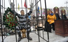 A girl looks at an installation set at a barricade of pro-EU opposition protesters in Kiev depicting Ukrainian President Viktor Yanukovych sitting on a gold toilet in a prison cage.