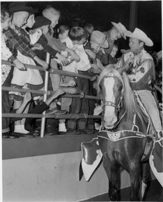 HOWDY, LITTLE PARTNER - Roy Rogers rides 'Trigger' around the perimeter of the arena to greet Houston rodeo fans - Sam Houston Coliseum - Houston, TX - 1960s.