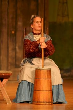 Here's a classic Aunt Eller at the butter churn.  Notice the pulled back hair, apron and use of age make up.