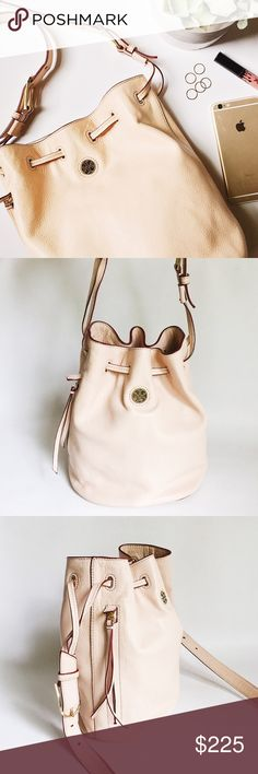 """Tory Burch Brody Leather Bucket Bag Tory Burch Brody Leather Bucket Bag in neutral beige pebbled leather featuring gold tone hardware.  Supple, relaxed leather. Interior side zip and side slit pockets.  Exterior zip pocket.  Small stain on bottom, see pic.  No other stains, damage or signs of wear.  Last pic stock photo in different color, used to show fit.  Measurements: 11.5"""" W x 11"""" H x 6"""" D Handle drop: 21"""" Tory Burch Bags"""