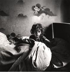 Sara, sitting in bed in a basement dwelling, with stenciled flowers above her head, Warsaw, ca. 1935–37 - Roman Vishniac