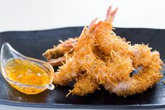 """Coconut Shrimp with Spicy Orange Sauce.  For those of you that have never had it, Coconut Shrimp is essentially shrimp that has been """"breaded"""" in shredded dried coconut before being deep fried. The golden brown tendrils of fried coconut not only provide a crisp crunch, they also contribute a wonderful nutty flavor that compliments the shrimp."""