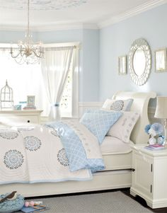 I really like this room with the decoration on the ceiling and the mirror reflecting the circles on the quilt.  super cute girls room in unexpected blue and white!