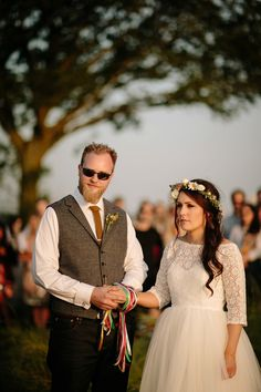 A handmade, Pagan handfasting on the family farm. The bride wears a 1950's inspried lace dress with 3/4 sleeves.  Photography by Tom Ravenshear.