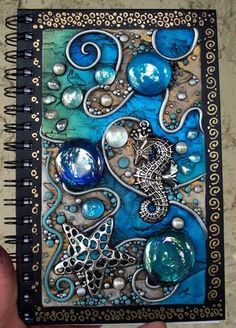Seahorse King journal --Mandarin Moon decorated this blank journal with polymer clay, pearls, iridescent glass gems, crystal droplets, metal starfish and seahorse, acrylic paint and PearlEx powdered pigments. The border was hand-painted with gold leaf pen.