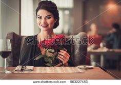 Elegant brunette lady with bouquet of red roses in restaurant