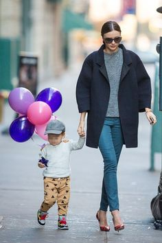 Heading to a Thanksgiving celebration with her son Flynn in New York, Miranda Kerr wore a navy coat with a grey jumper, teal jeans and red printed heels