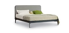 The bed Suite has the headboard padded in fabric with leather piping and black lacquered metal feet. The headboard with panels in different sizes, set up a practical bed of great elegance.