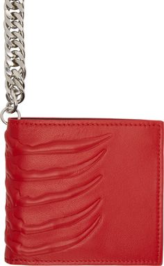 """Alexander McQueen Grained leather bifold wallet in red. Embossed ribcage detail at front, back, and fold. Silver-tone fixture strap with signature skull charm and lobster clasp closure. Tonal crystal accents at skull pendant. Contrasting interior in black. Card slots, note compartments, coin pocket with press-stud closure, and embossed logo at wallet interior. Tonal stitching. Approx. 4.25"""" length x 4"""" height."""