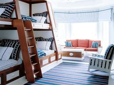 With double beds below and twins above, this nautical-inspired bunk room can sleep six. Built-in cabinetry along the sides and below makes it easy for kids to keep the room tidy. (Photo: Photo: William Waldron; Designer: Diamond-Baratta designers)